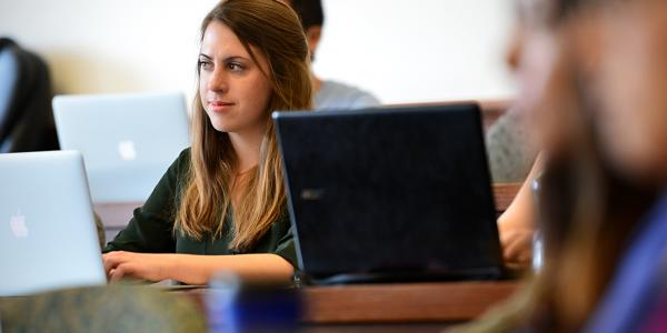 students taking notes on their laptops in a classroom